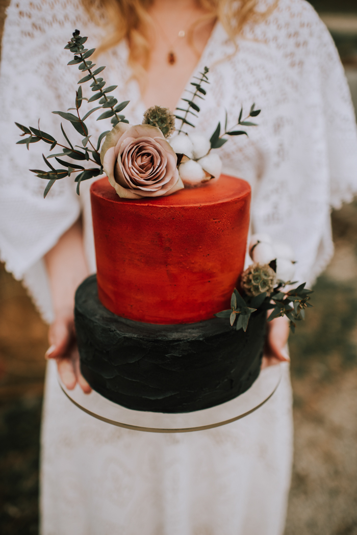 The wedding cake was a rust and black one, with greenery, a blush rose and cotton on top