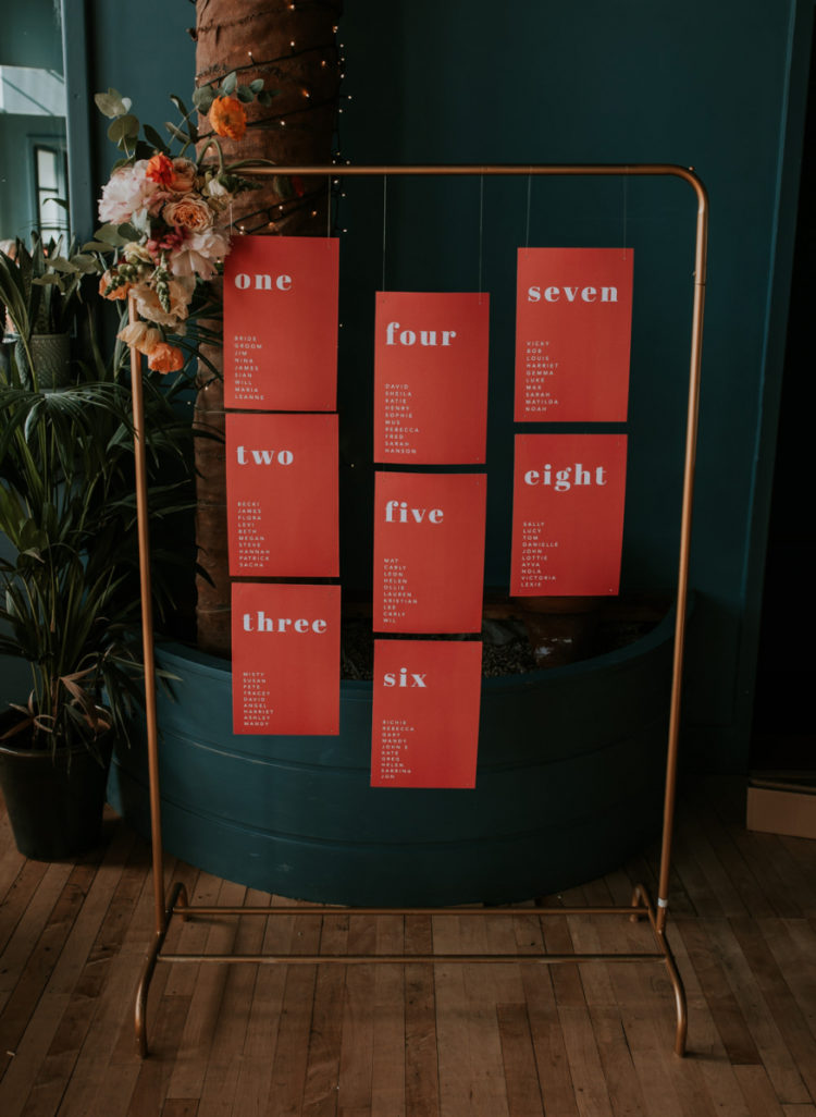 The wedding seating chart was done with a copper frame and coral table sheets hanging