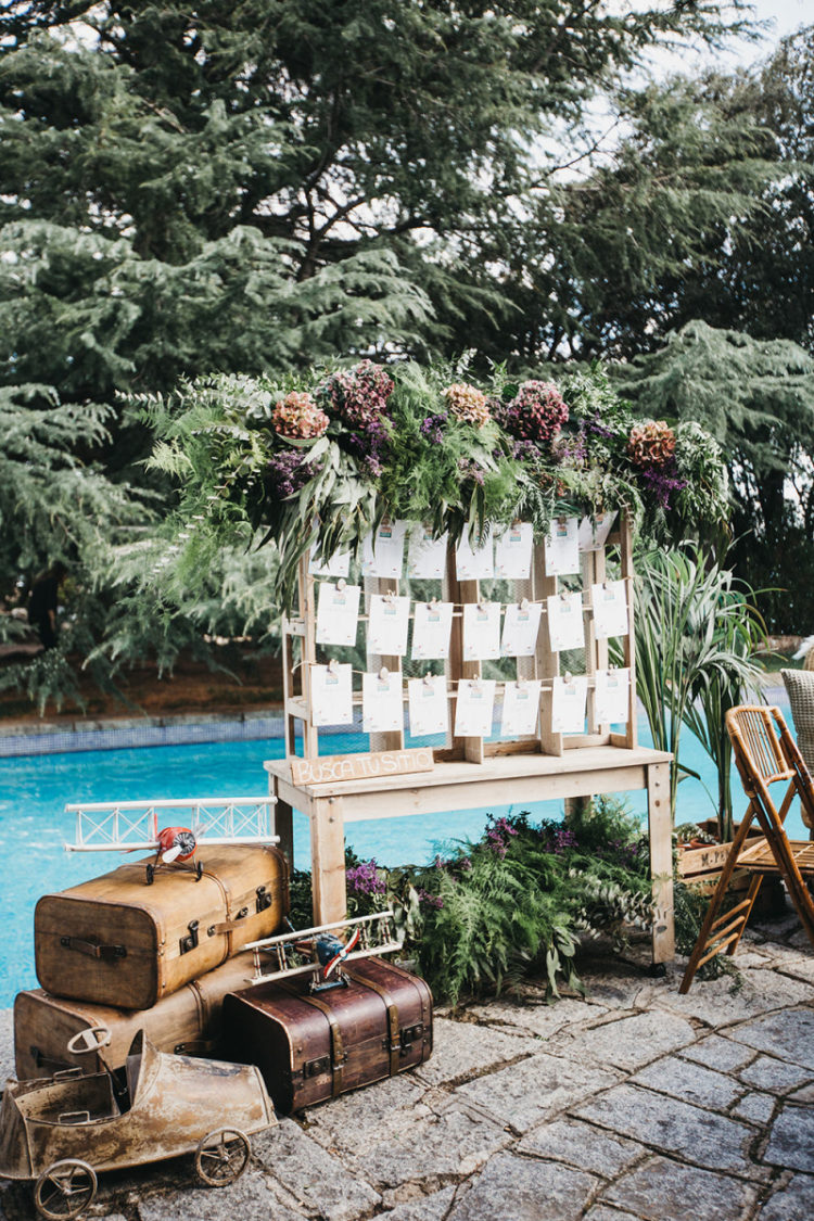 The wedding seating chart was done with lush greenery, dried blooms and a stack of vintage suitcases