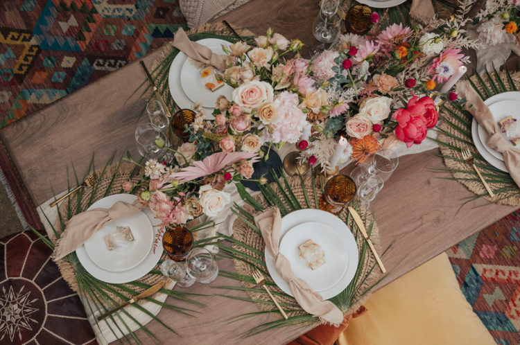 The wedding tablescape was done with wicker chargers, palm fronds, lush pink and blush blooms and pampas grass