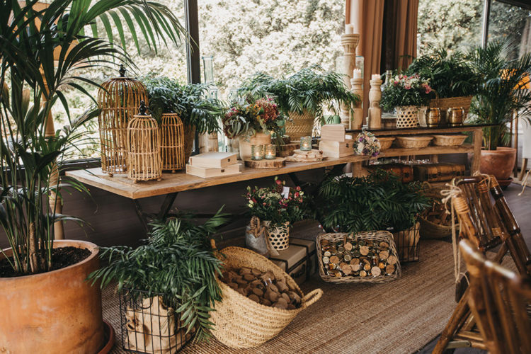 The venue features both rustic and boho decor, lush greenery and wooden decorations