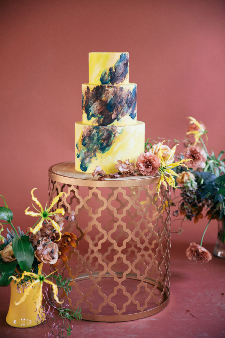 The wedding cake was done in bright yellow and decorated with dark and pastel brushstrokes