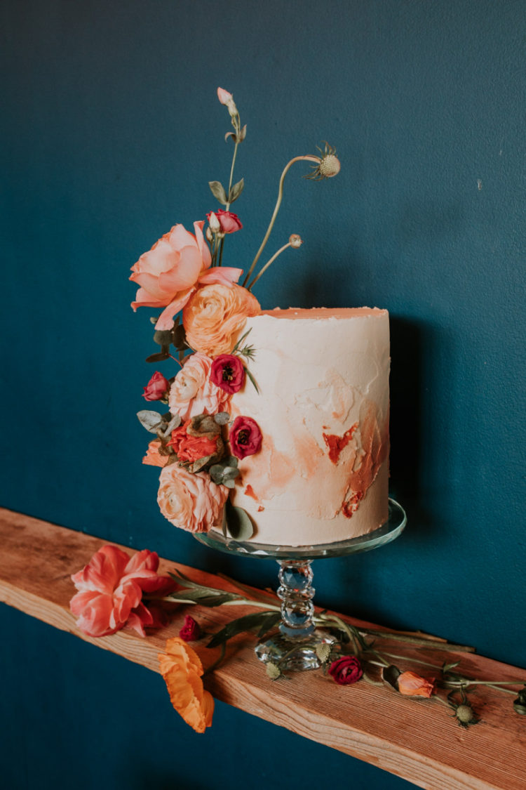 The wedding cake was textural and ombre coral, with fresh coral blooms on its side