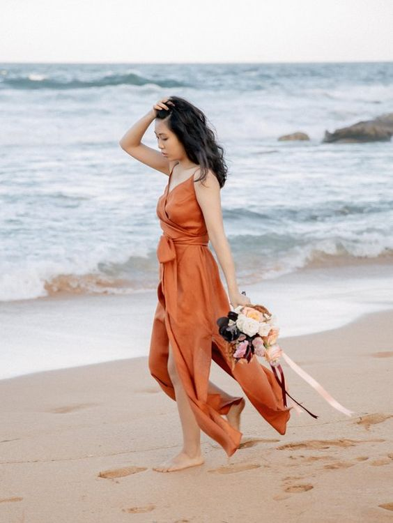 a paprika colored wedding dress with a wrapped and tied up bodice, spaghetti straps and slits for a fall beach bride