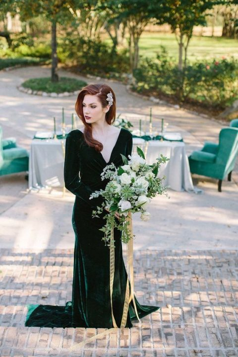 a beautiful forest green velvet wedding dress with a deep neckline, long sleeves and a train looks super exquisite