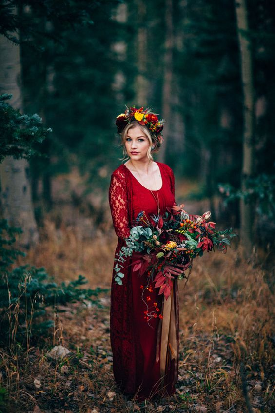 a deep red wedding dress with lace sleeves, a cutout neckline and a bright floral crown for a rustic fall bride