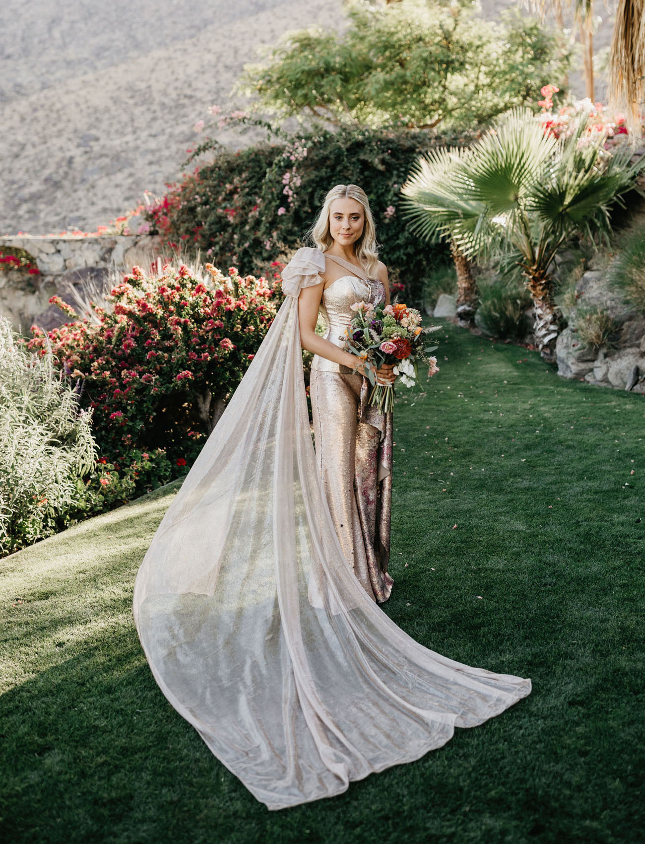 The bride was wearing a unique custom jumpsuit with a bustier, sequins and a long capelet with a train