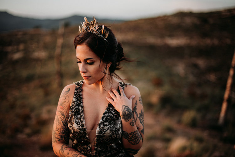 The bride was wearing a black lace wedding dress with thick straps, a covered plunging neckline and a gorgeous leafy headpiece