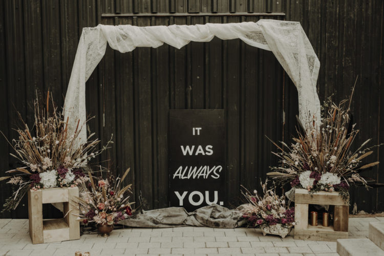 The wedding arch was decorated with white lace, dried herbs and fresh pink and fuchsia blooms and some candles