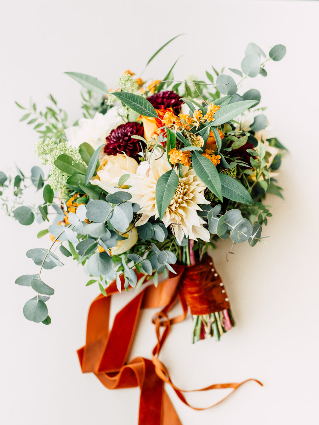This lovely wedding bouquet was done with burgundy, orange and creamy blooms and a bright orange ribbon