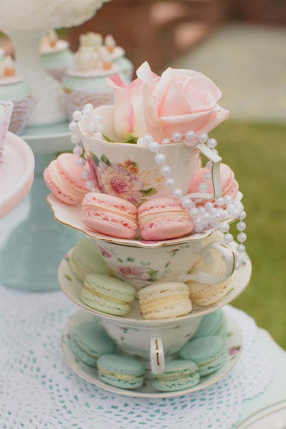 a beautiful wedding or bridal shower centerpiece made of vintage teacups, colorful macarons and pearls plus a bloom