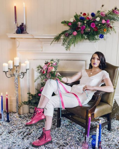 a daring and edgy bridal look with a white jumpsuit with beaded sleeves, pink boots and a moody purple lip