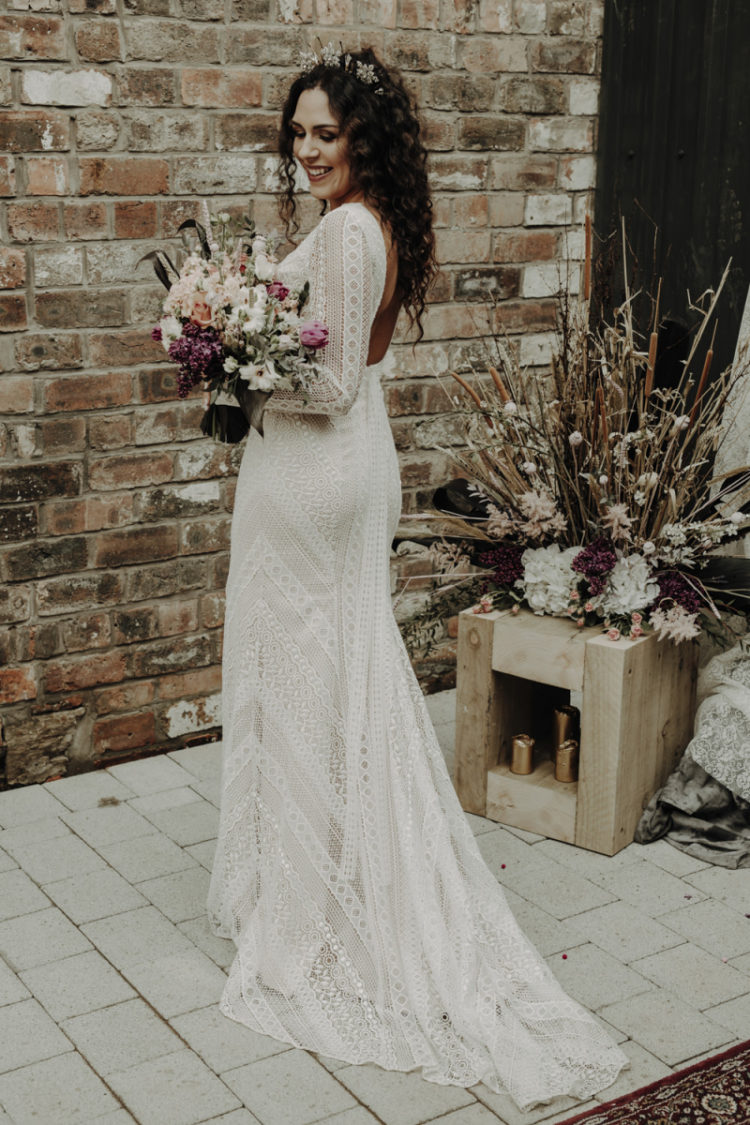 The bride was wearing a boho lace sheath wedding dress with long sleeves and a cutout back plus gorgeous headpieces