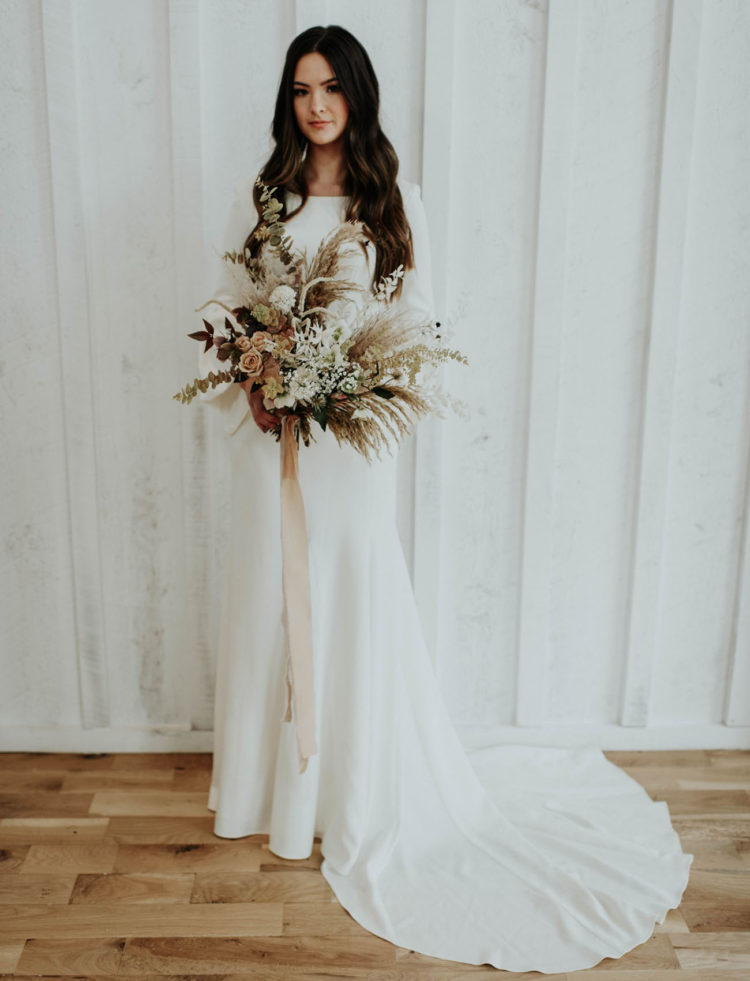The bride was wearing a modern wedding dress with a high neckline, bell sleeves and a train