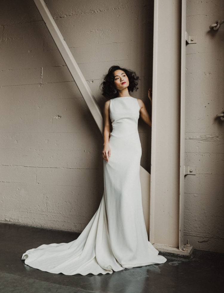 The bride was wearing a plain fitting sleeveless wedding dress with a train