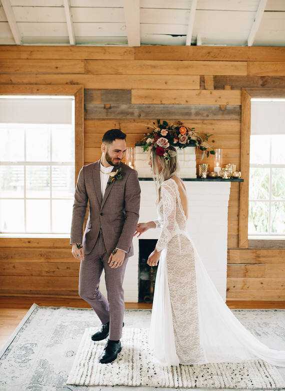 The bride was wearing a unique lace wedding dress with an open back and long sleeves plus a train