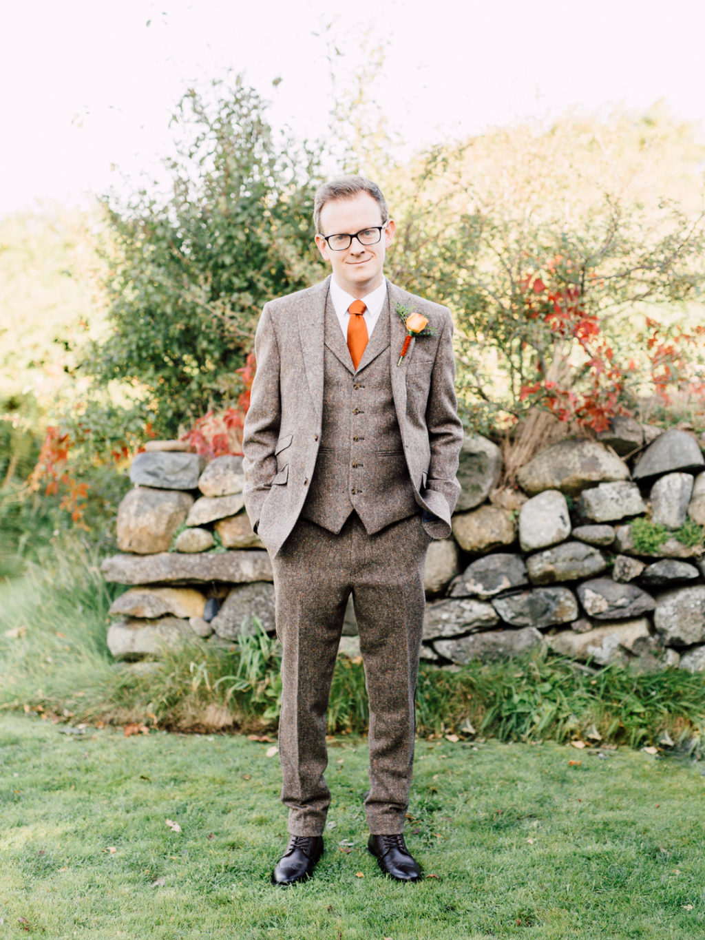 The groom was rocking a three piece tweed suit with a bright orange tie and black shoes
