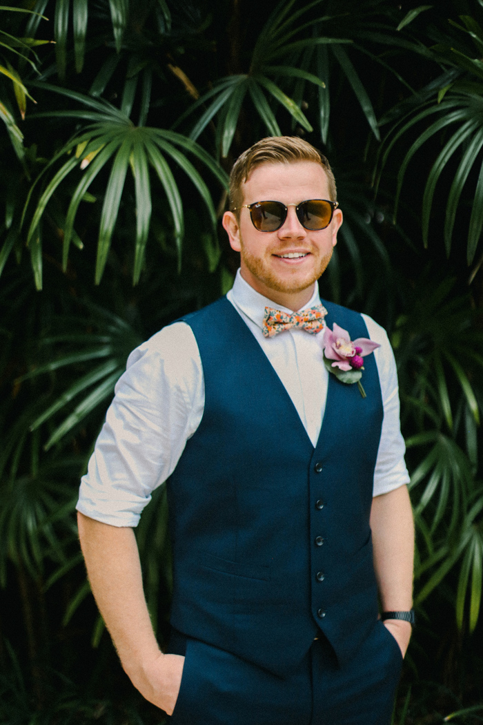 The groom was wearing navy pants, a waistcoat and a colorful bow tie