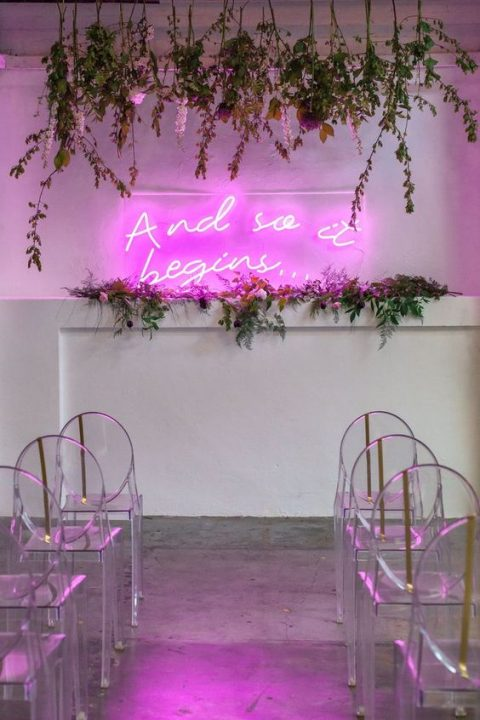 a chic modern wedding ceremony space with a pink neon sign, greenery, hanging blooms and acrylic chairs