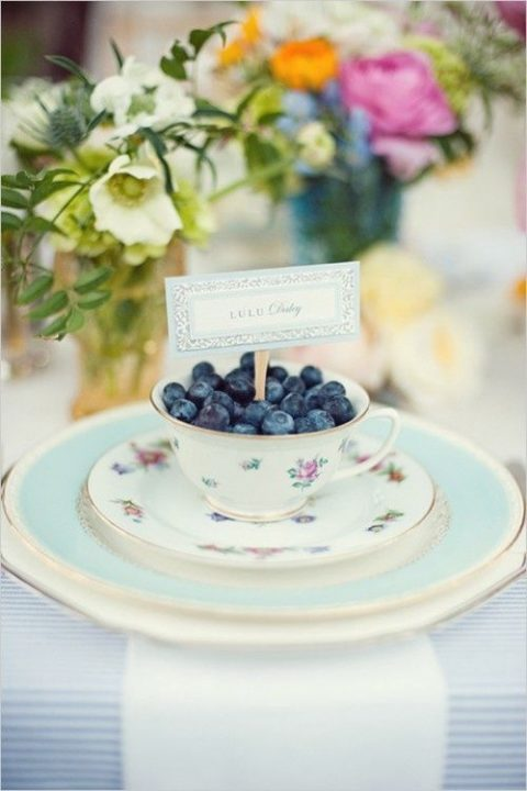 a chic vintage inspired place setting in aqua, with a floral teacup and blueberries inside plus a card