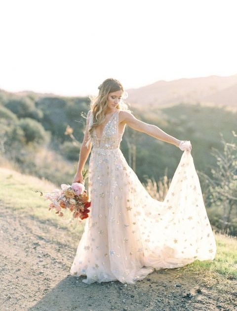 a gorgeous wedding gown with shiny stars and a plunging neckline plus a train for a celestial bride