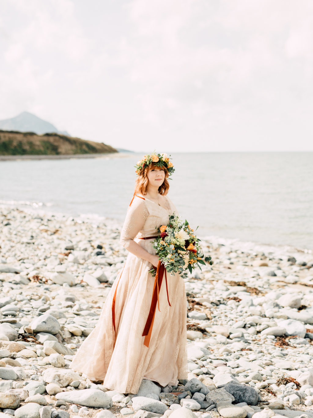 The bride was wearing a neutral lace wedding dress with illusion sleeves and a floral crown
