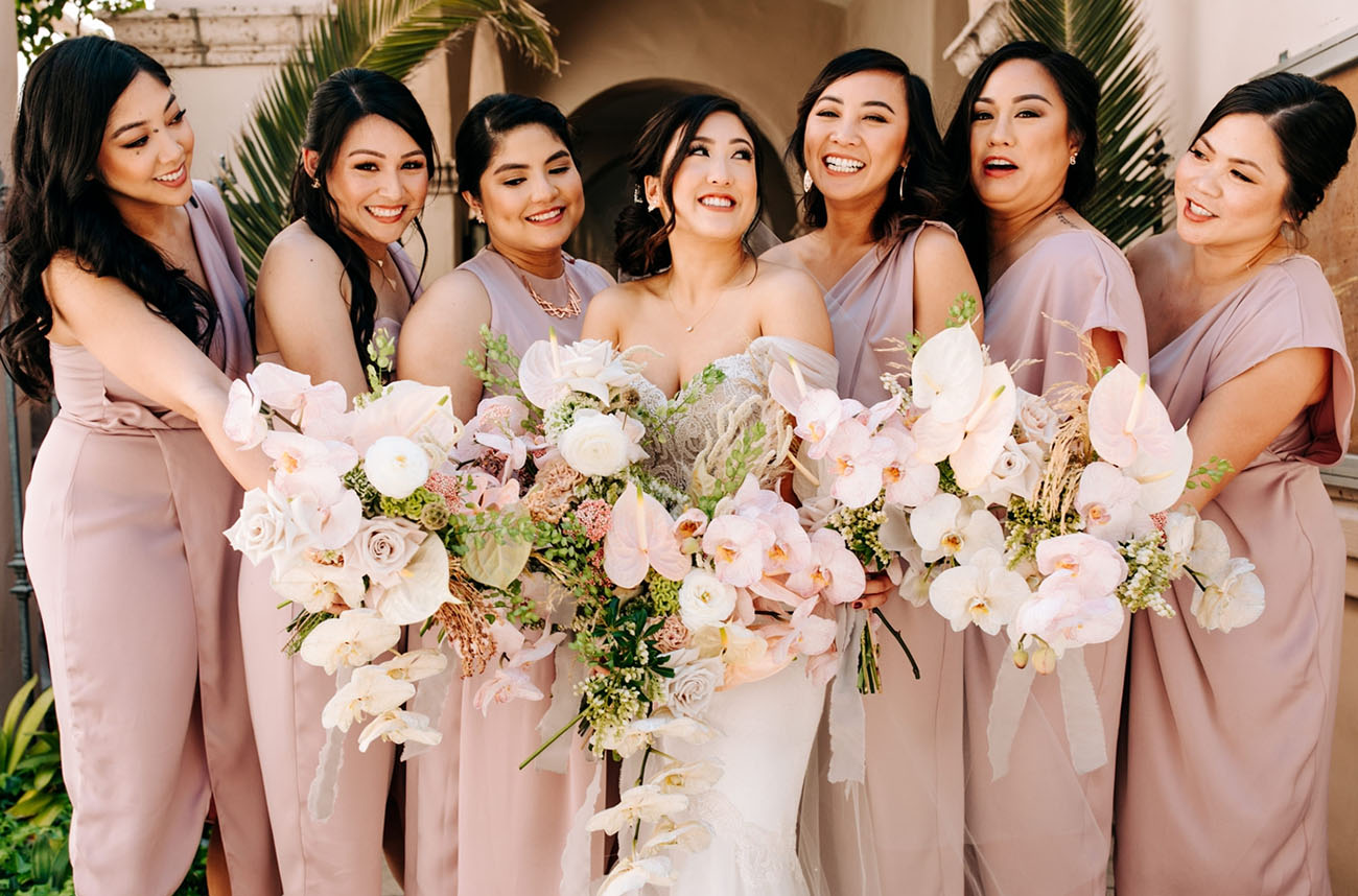 The bridesmaids were rocking mismatching mauve dresses and carried beautiful bouquets in blush