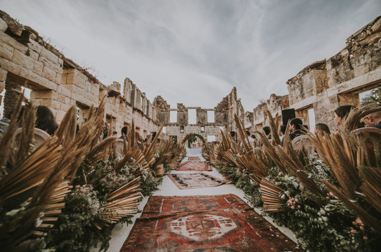 The ceremony space was done with boho rugs, greenery, fronds and grasses