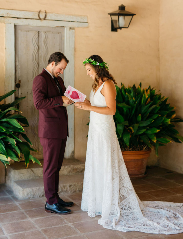 The groom was wearing a burgundy suit and black shoes, the bride was wearing a white boho lace A-line dress with a train