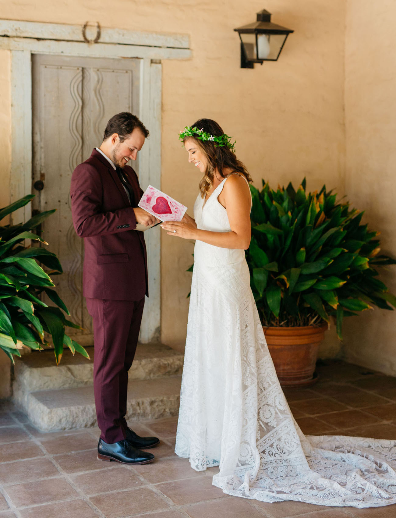 The groom was wearing a burgundy suit and black shoes, the bride was wearing a white boho lace A line dress with a train
