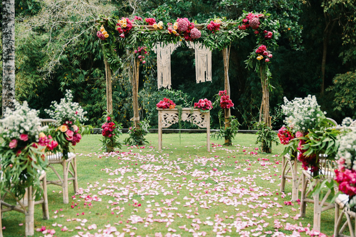 The wedding ceremony space was done with a wooden arch, macrame, bright blooms and chairs decorated with the same florals