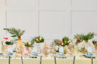04 The wedding tablescape was done with a yellow tablecloth, colored glasses and vases, ombre vases and blue plates plus greenery and bright tropical blooms