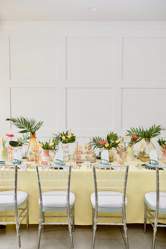 The wedding tablescape was done with a yellow tablecloth, colored glasses and vases, ombre vases and blue plates plus greenery and bright tropical blooms