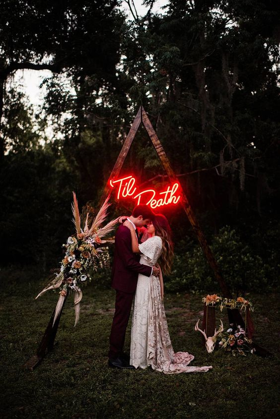 a boho wedding arch with lush florals, dried grasses and skulls and a red neon sign