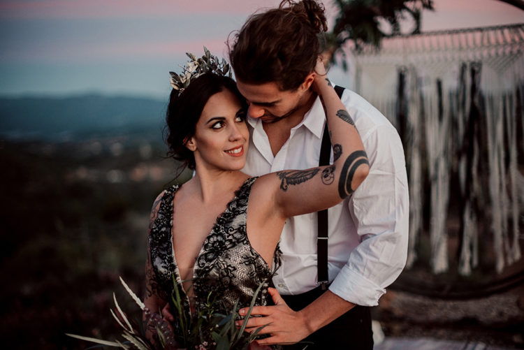 the groom was wearing simple black pants, a white shirt and black suspenders and a messy man bun