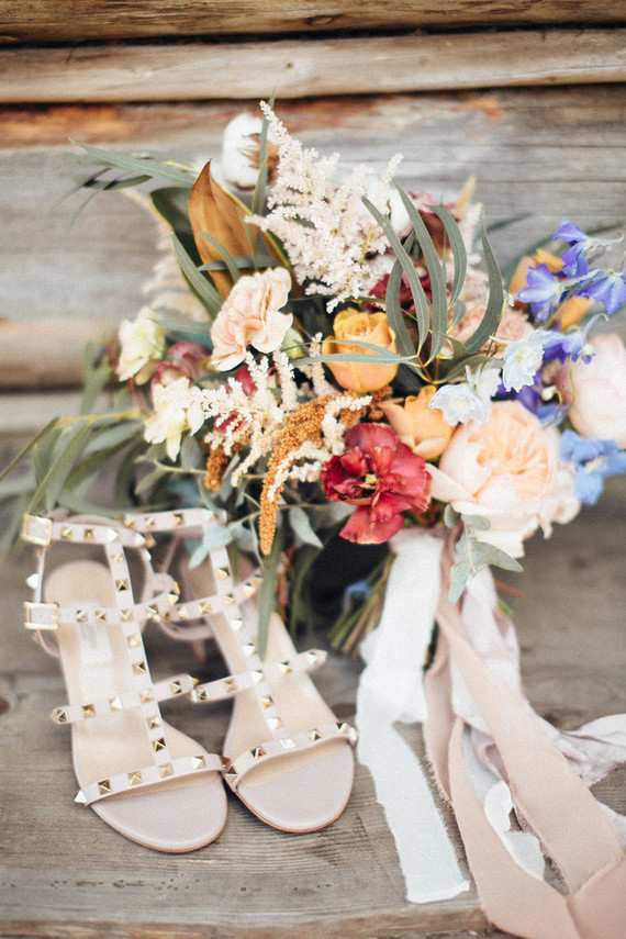 The bride was wearing studded strappy heels and carrying a bright and textural wedding bouquet