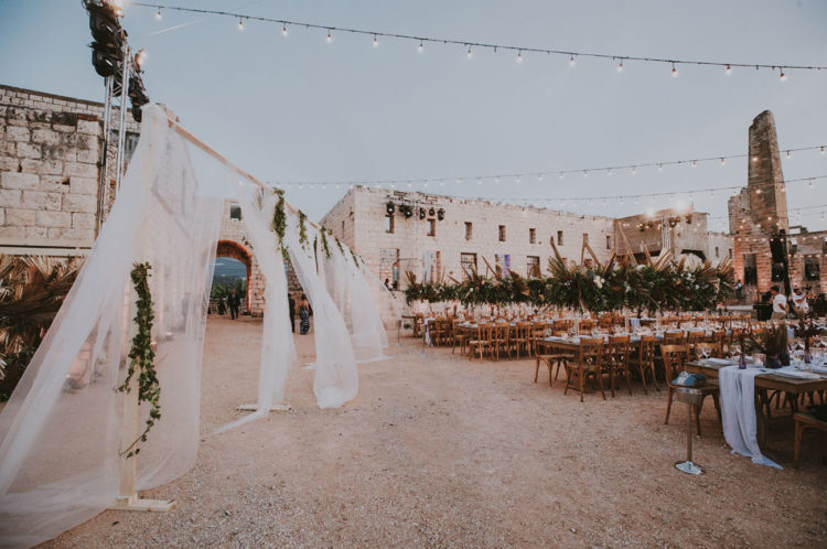 The reception took place under the stars and was decorated with greenery and fronds, too