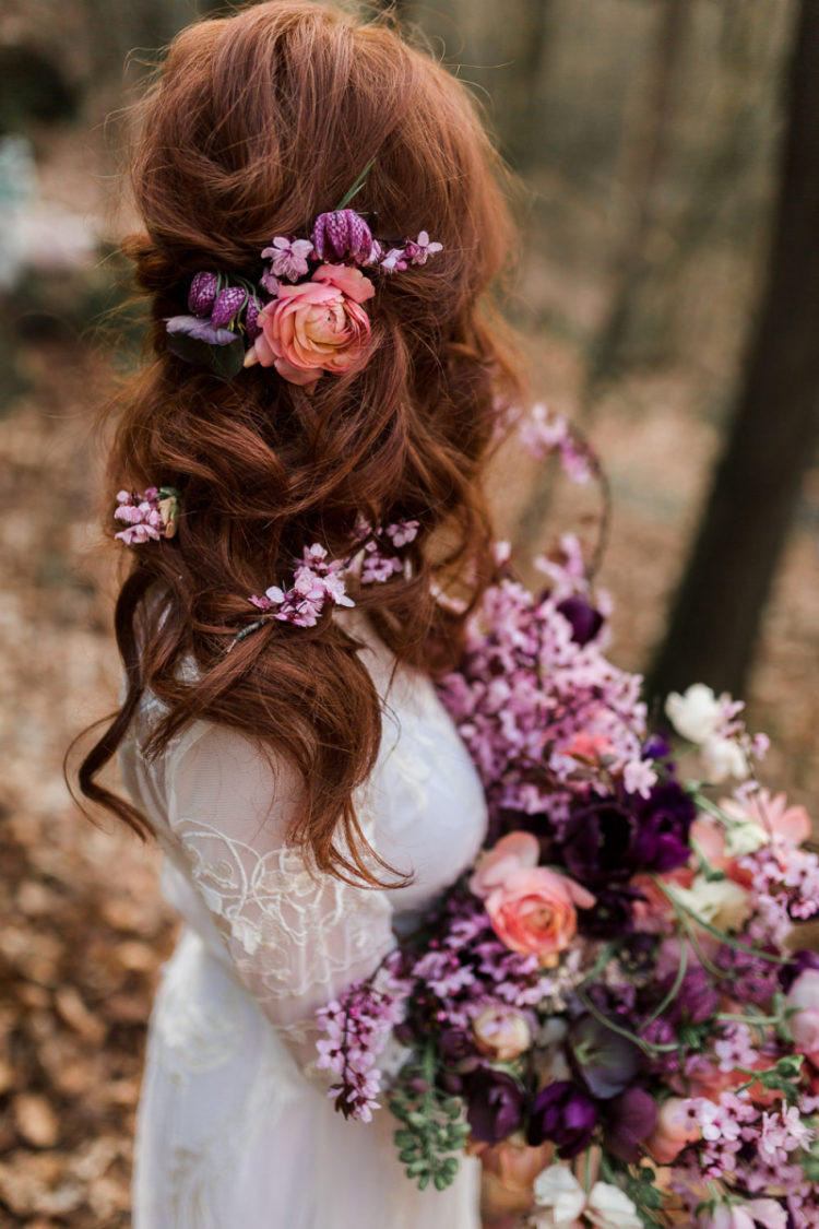 The wavy and relaxed wedding hairstyle was spruced up with purple and orange blooms