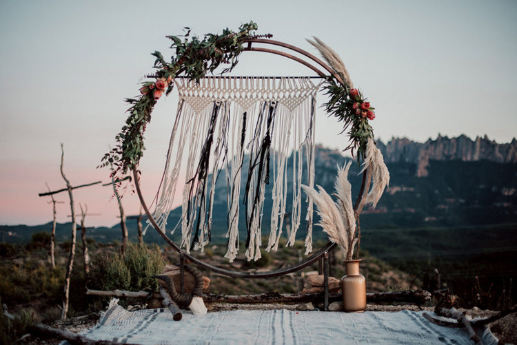 The wedding arch was a metal moon gate decorated with fresh blooms, greenery and grasses and macrame