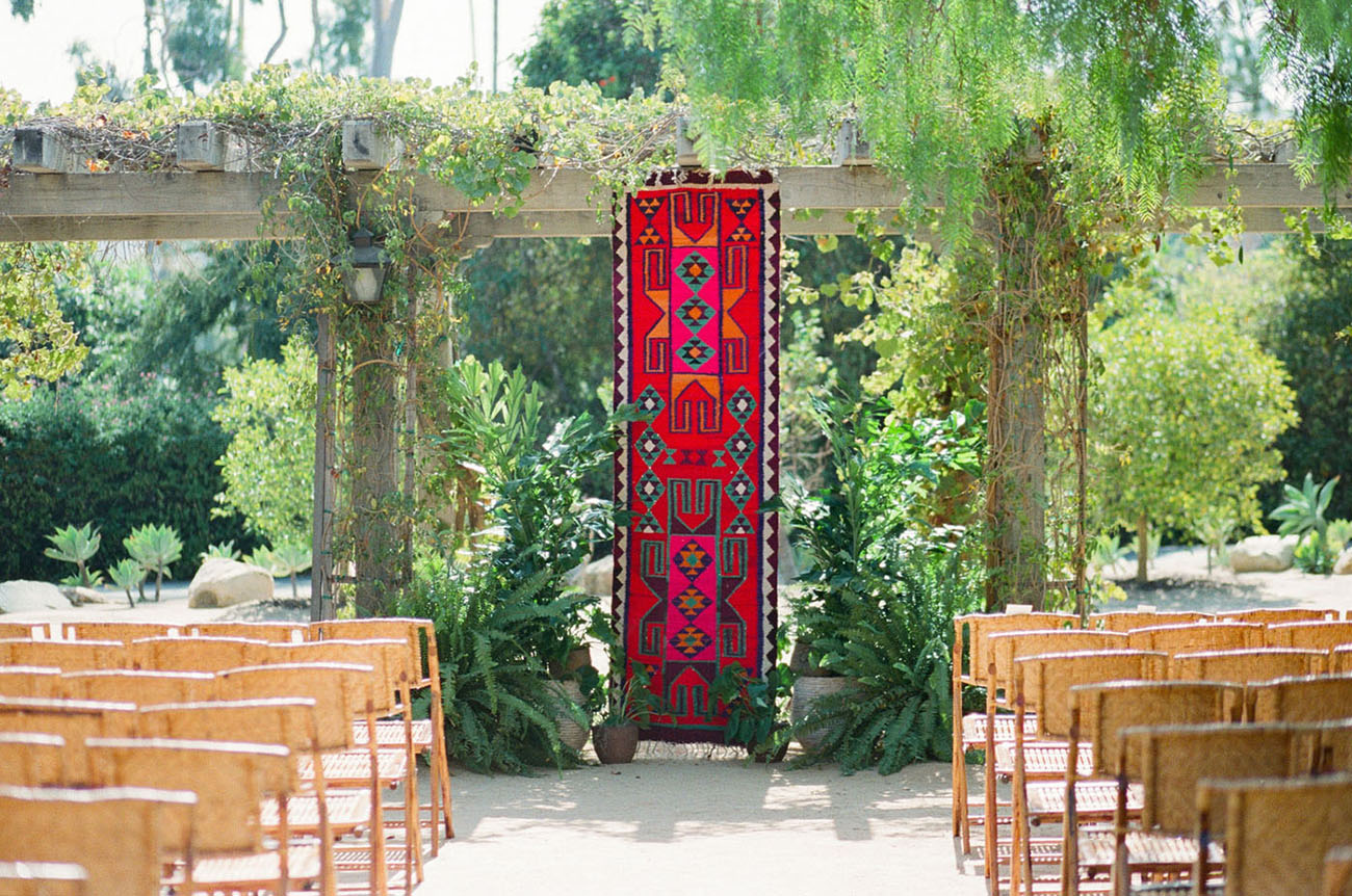 The wedding ceremony space was done with a bright and colorful embroidered hanging