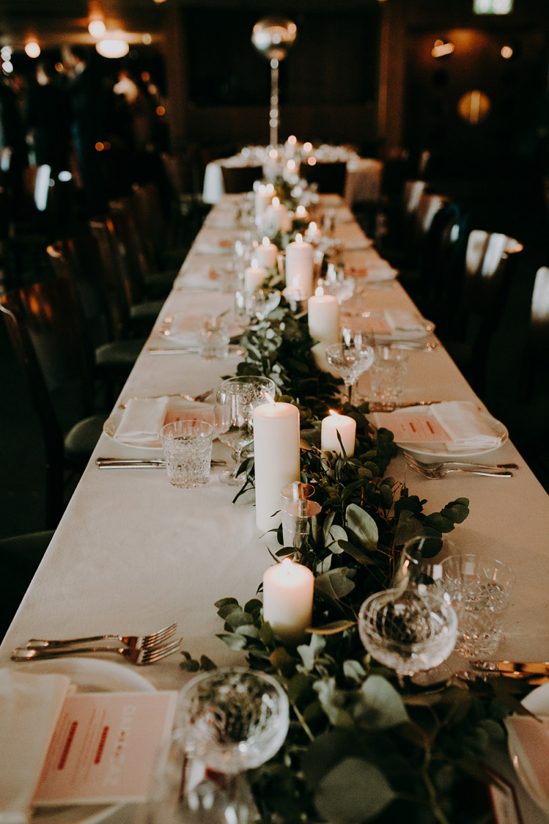 The tablescapes were done in neutrals, with fresh greenery and pillar candles to create a mood