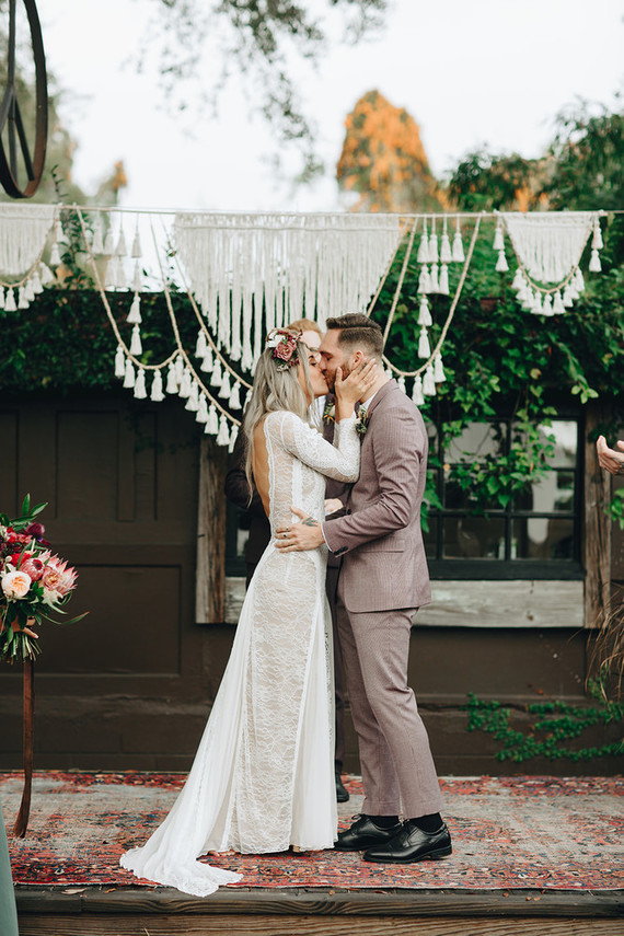 The wedding ceremony space was done with a tassel wedding arch and some blooms