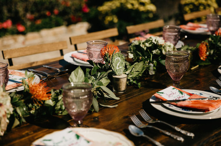 The wedding tables were done with greenery, bold blooms, cacti, colored glasses and napkins