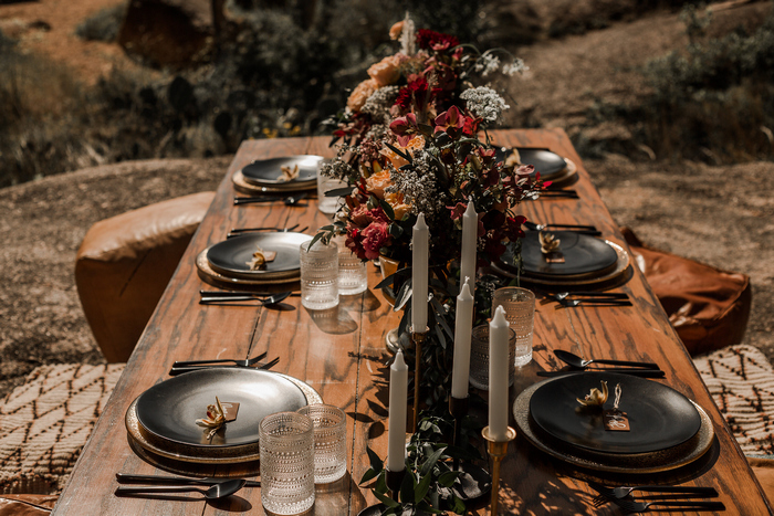 The wedding tablescape was done with dark plates and chargers, with neutral candles and bold and dark blooms