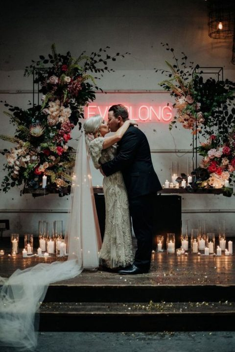 a fantastic wedding ceremony space with lots of candles, lush blooms and greenery and a neon sign