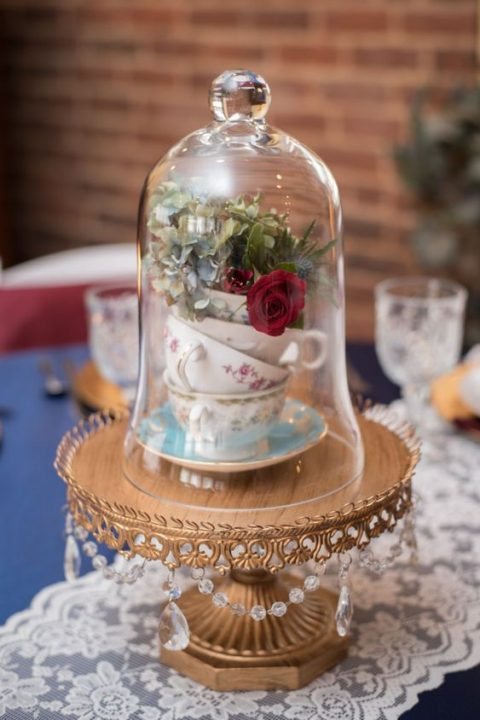 a refined wedding centerpiece with a gold stand with crystals, a stack of teacups with blooms in a cloche