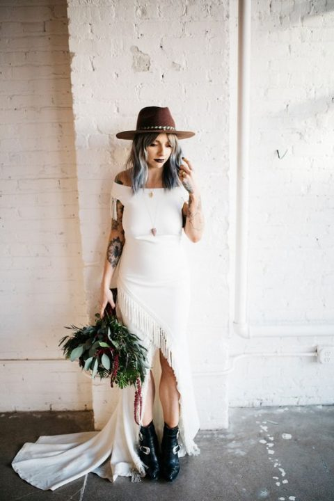 an off the shoulder wedding dress with an assymmetrical fringe skirt, black leather boots and a brown hat