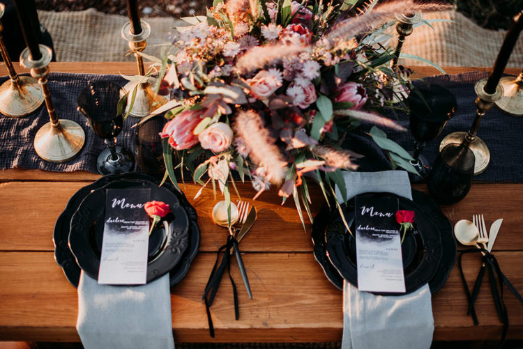 Black candles and chargers, a graphite runner, bold bloos and gilded touches made the wedding decor amazing