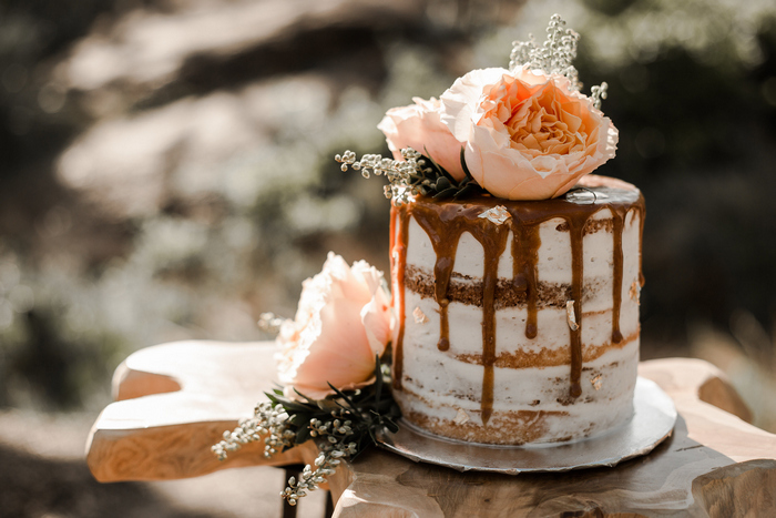 The first wedding cake was a naked one, with caramel drip and fresh blooms on top