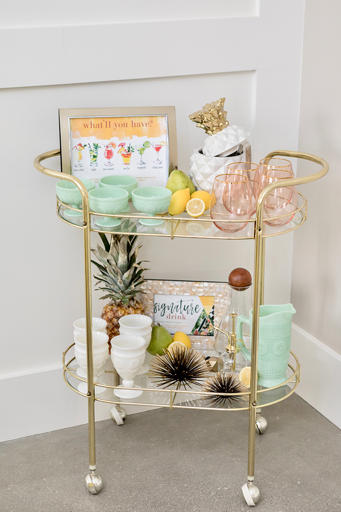 The wedding bar cart was a glass and gold one, with pastel tableware, fruits and a colorful cocktail menu